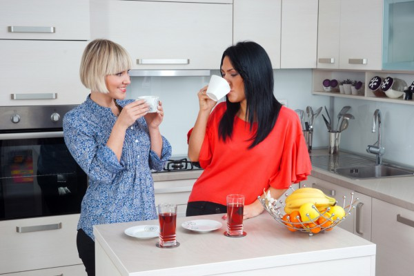 two attractive woman friends drinking coffee and chatting in kitchen